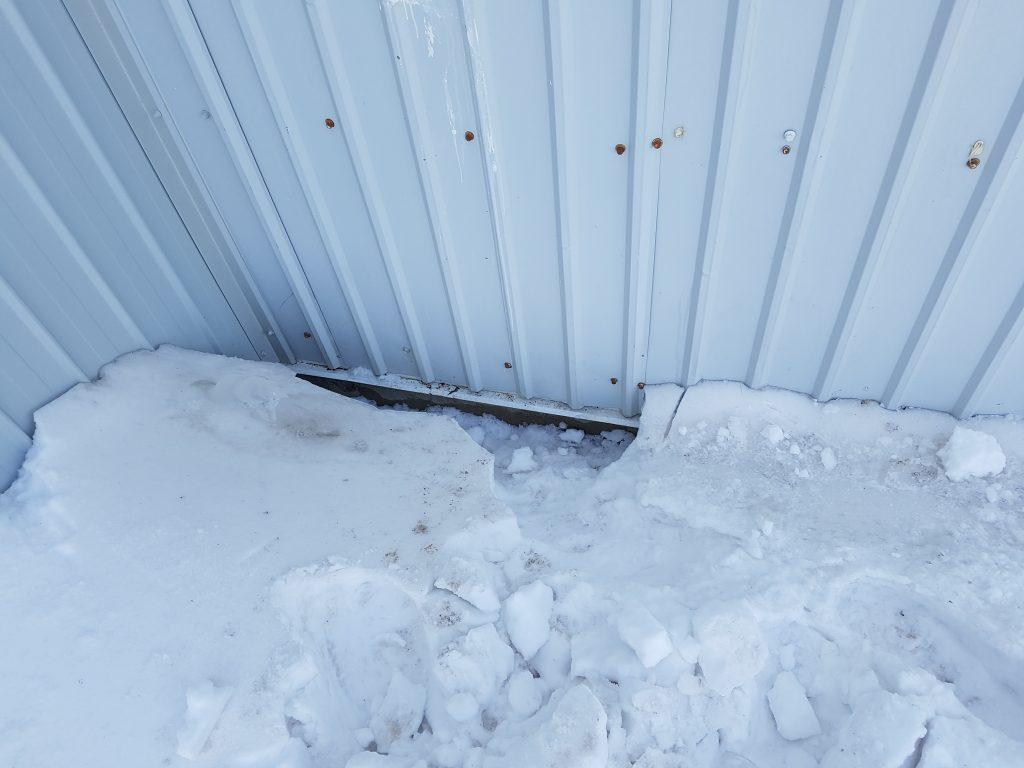 Hole under the snow drift where kitten was stuck